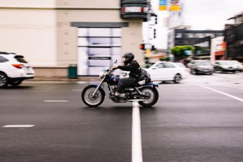 man rides a motorcycle down a street