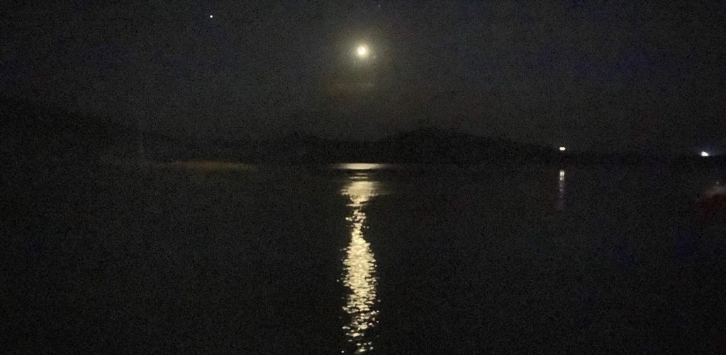 Moon above a large body of water